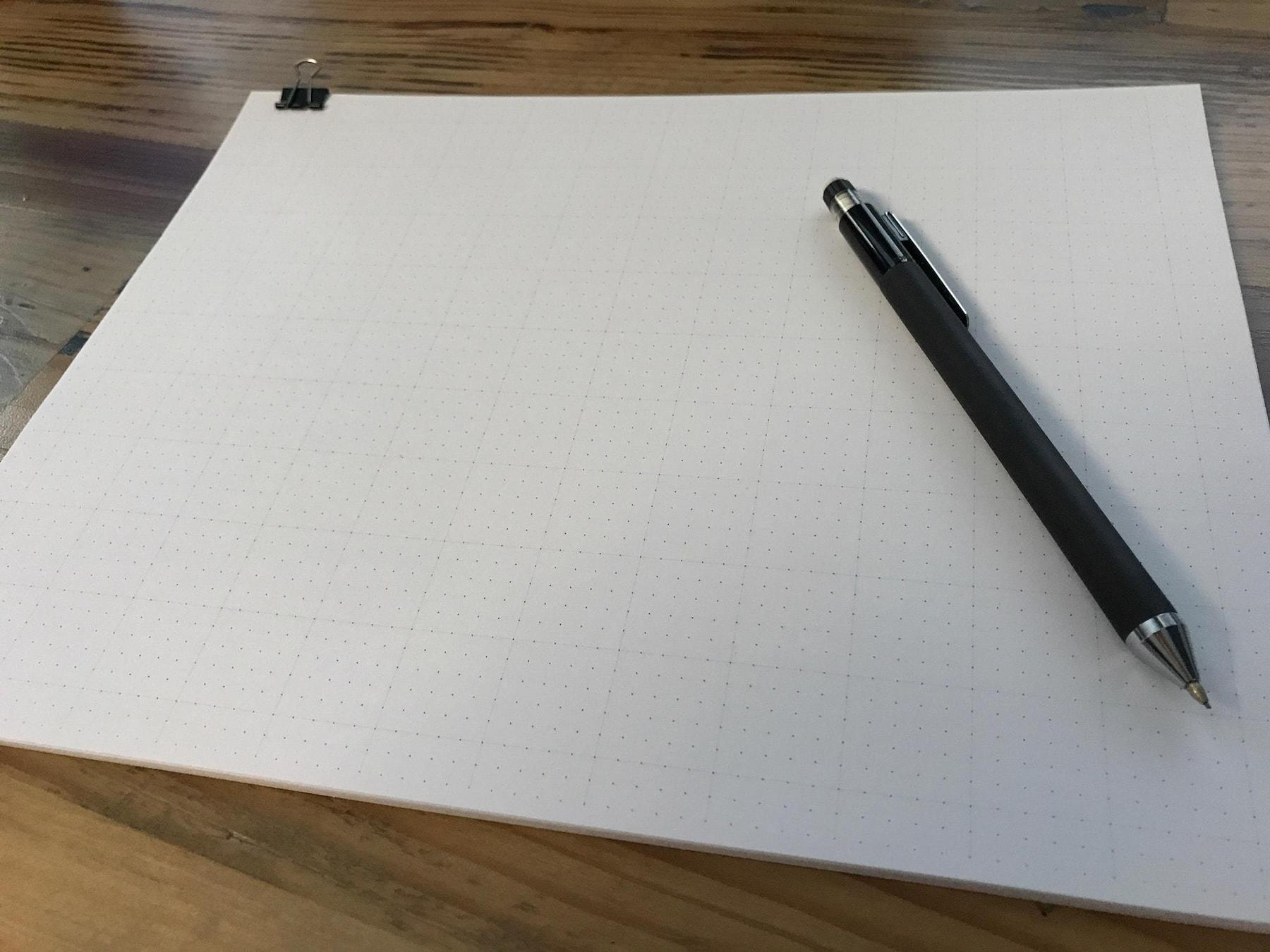 Dot paper on a desk with a mechanical pencil